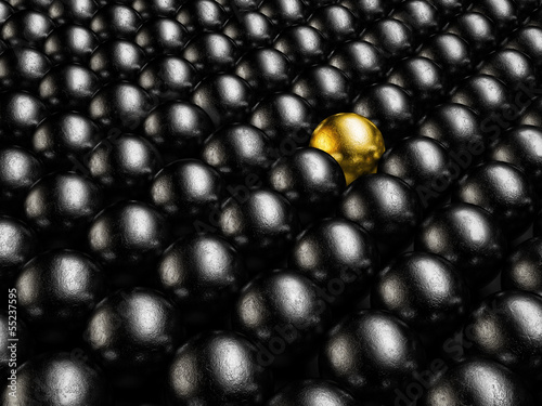 A gold ball in many metal balls