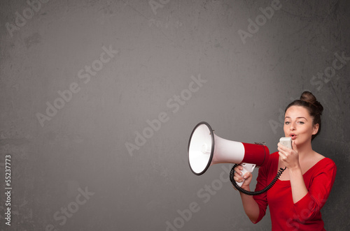Girl shouting into megaphone on copy space background