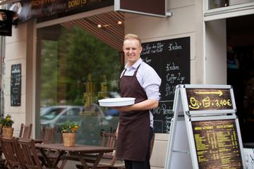 Lächelnder Kellner vor dem Straßencafe
