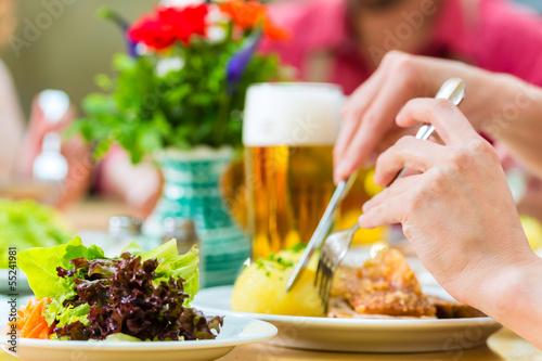 Leute in Bayerischer Tracht essen in Wirtschaft