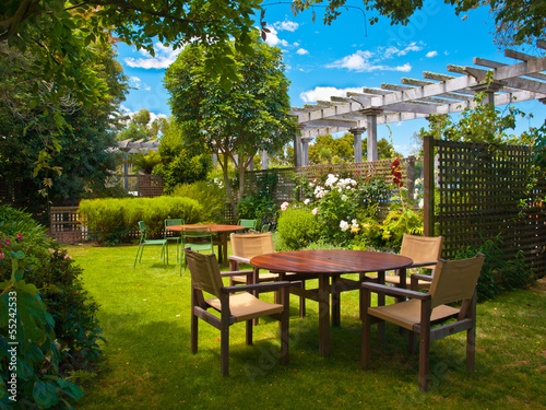 Fotobehang Tuin dining table set in lush garden