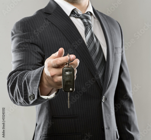 Elegant businessman holding car key in his hand