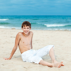Portrait of teenage sitting on sand near sea