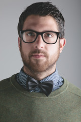 Modern man wearing black bowtie on grey background.