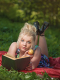 The girl lays on a glade, reads the book and eats an apple