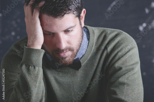 Stressed teacher man in front a blackboard.