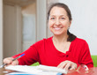 gladful mature woman fills in documents