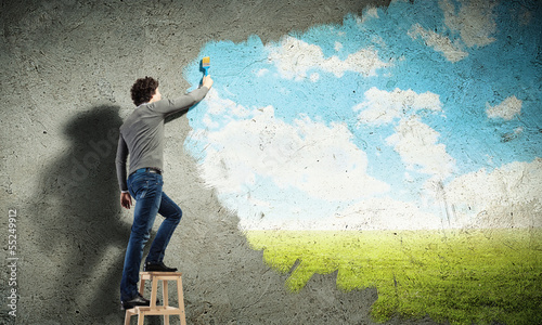 Young man drawing a cloudy blue sky