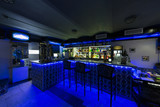 bar counter with chairs illuminated with blue light