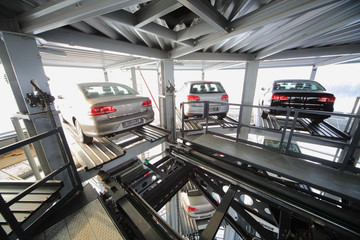 Three vehicles on the top floor of a transparent construction