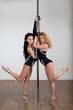 Two young beautiful dancer dancing with a pole