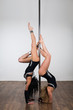 Two dancer doing difficult acrobatic tricks with a pole