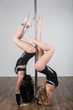 Twol dancer doing acrobatic tricks with a pole