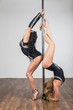 Two dancer doing acrobatic tricks with a pole