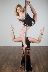 Tw dancer doing difficult acrobatic tricks with a pole