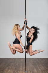 Two young girls doing acrobatic tricks with pole hanging
