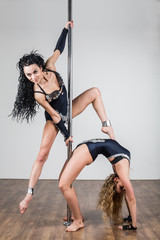 Two flexible girls doing difficult acrobatic tricks with pole
