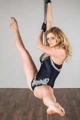 Beautiful dancer doing difficult acrobatic tricks with pole