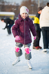 Little girl in knee pads skating at the rink in winter