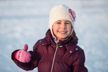 little girl skating at rink in winter and showing thumbs up