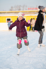 Smiling little girl in knee pads skating at rink in winter