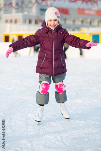 Little girl in knee pads skating at the rink