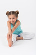 Girl doing gymnastics exercise sitting on the floor