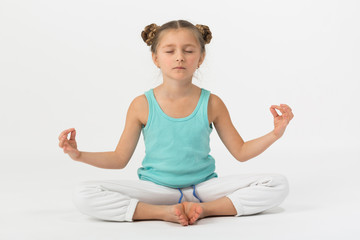 Girl doing is sitting with eyes closed in lotus position