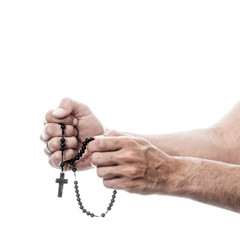 male hands praying with rosary