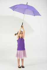 A girl in a purple clothes with departing from the wind umbrella