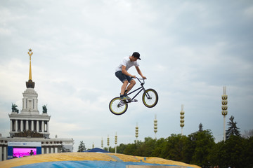 Young man jumps on bike