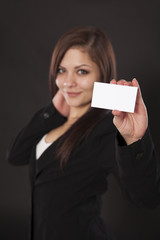 Young woman in a vest holds up a business card.