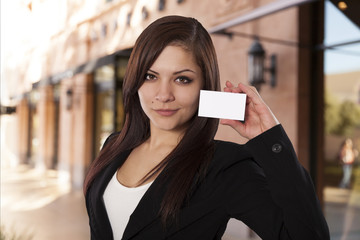 Young business woman holds up a blank business card.