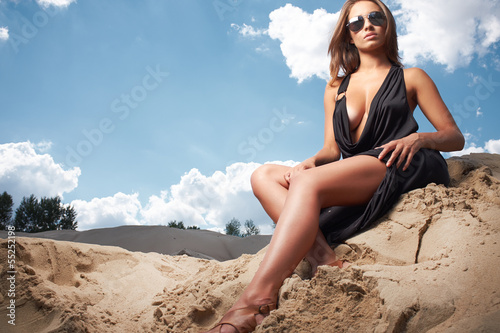 Beautiful girl wearing black dress sitting on the sand