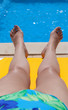 Legs of a woman relaxing poolside