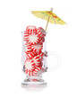 Peppermint candy in glass and cocktail umbrella isolated,