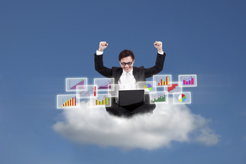 Happy businessman looking at bar graphs on cloud
