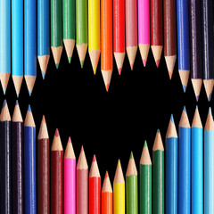 Back to school. Colorful pencils arranged as heart on black