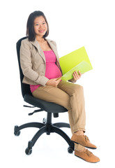 Pregnant Asian business woman working