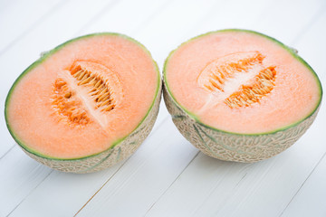 Two halves of cantaloupe melon on white wooden boards