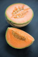 Ripe cantaloupe melon over dark wooden background