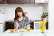 beautiful asian woman eating in the kitchen