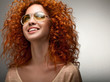 Red Hair. Beautiful Woman with Curly Long Hair and Sunglases