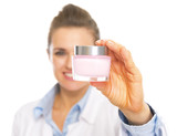 Closeup on cosmetologist woman showing bottle of creme poster
