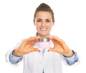 Smiling cosmetologist woman showing bottle of creme