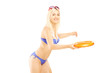 Smiling female in bikini playing with frisbee