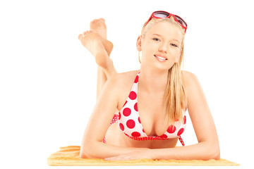 Smiling blond female lying on a beach towel and looking