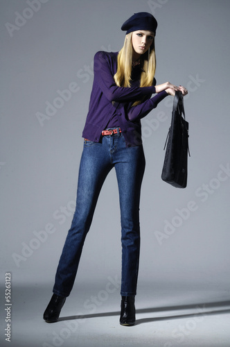 full-length portrait of fashion model in hat with bag posing