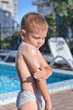 Little boy applying sunscreen