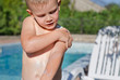 Young boy carefully applying sunscreen